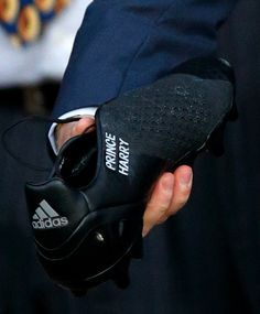 7dafed199ce78a Prince Harry is presented with a pair of rugby boots with his name stitched  into them