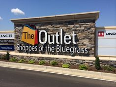 The Outlet Shoppes of the Bluegrass Monument Sign located in Simpsonville, Ky. This sign features a stone monument with channel letters that is flanked by two 65ft long monument signs with tenant panels. #theoutletshoppesofthebluegrass #outletsinkentucky #simpsonvilleky
