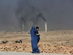 A woman walks past a local brick factory as she carries her son on the outskirts of Kabul.  Rahmat Gul, AP