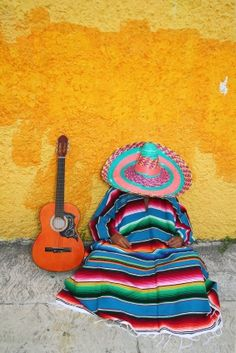 A Mexican setting.  Man or woman next to their guitar.