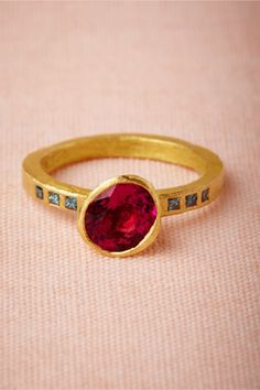 Vermilion Ring: The rubellite is a rare red tourmaline that meets a certain color criteria; while most gemstones change their color depending on the light source, the rubellite shines just as intensely in artificial light as it does in daylight. Here, an enchanting red rubellite stone is set between three blue princess cut diamonds on each side,18k yellow gold, 1.10 ct rubellite, blue princess cut diamonds. Handmade in France. $2,600