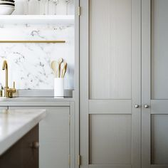 One cannot go wrong with a mix of marble and brass finishes. This elegant kitchen's brass and marble accents add feminine flair to the muddy gray cabinets.
