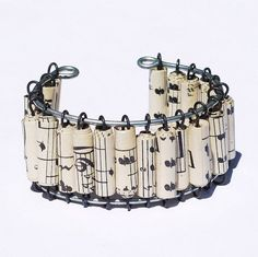 Paper Bead Jewelry by Tanith Rohe  This cuff style bracelet features hand rolled paper beads made from  vintage sheet music. The beads are on annealed steel wire strung on  galvanized steel wire. This...