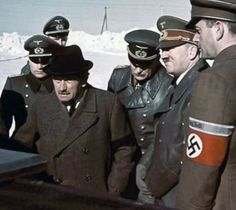 Founder of the famous automaker which bares his name, Ferdinand Porsche gives Adolf Hitler, Reichsminister of Munitions Albert Speer, and accompanying entourage of military leaders a demonstration of his latest innovations for the Panzer tank during a visit to the Eastern Front in the Spring of 1943.
