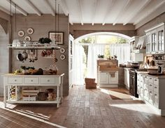 A nice, spacious neutral kitchen. I love the big bright windows at the end and the pretty wood flooring. I am also a huge fan of white kitchen cupboards with the glass.