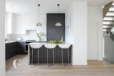 Modern black and white kitchen features white flat front upper cabinets and…
