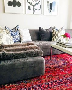 Decorating with Oriental & Persian Rugs -- Love this gorgeous living room with a gray faux suede sectional sofa, patterned gray and white throw pillows, a white marble topped coffee table and bright red embroidered and hand-knotted Persian area rug.