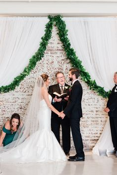 Emilie & Rusty's ceremony included a beautiful drapery lined in greenery. Simple & elegant! | Photo: Taylor Dane Photography | Florals: Forever Wild Floral Co | BridgeStreet Gallery & Loft | Birmingham Weddings
