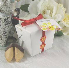 """Fortune Cookie Take Out Box Wedding Favor features an Asian take out box style favor box complete with wire handle. It is filled with a milk chocolate dipped fortune cookie. The box is decorated with a red satin ribbon and two Chinese """"double happiness"""" stickers. The look is complete with an Asian floral favor tag.  The tag can be personalized."""