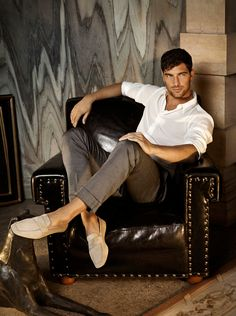 I love this look, although I wish the pants were either cuffed, or hemmed, not just rolled up. The loafers are beautiful. I also love the wall behind him, both the the grey patterned stone/wallcovering, and the yellow stone. But the club chair is not a great choice, and the shiny leather looks inexpensive, not luxurious.