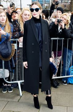 Olivia Palermo wears a pinstriped matching suit set, a black duster coat, black booties, and a blue fur clutch