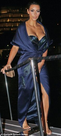 Showing some skin: Kim flashed her legs thanks to the split in her dress as she teetered around in her gold chain sandals