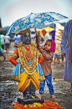 True Devotion  The boy holds an umbrella for beautiful idol of God Vitthal