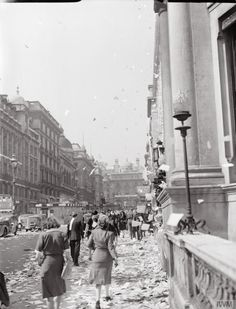 Civilians walk amongst the piles of torn up paper which have been thrown, 'ticker tape'-style, from the windows of offices, on Lower Regent Street, London, to celebrate the signing of the Peace with Japan.  More paper can be seen fluttering down onto the pavement and road: many vehicles appear to have stopped.  It appears that this photograph was taken on Lower Regent Street, looking back up towards Piccadilly Circus.  In the middle of the road (left of the photograph), a brick surface…