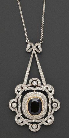 Edwardian Platinum and Diamond Pendant/Brooch, Marcus & Co., the scrolling form set throughout with old European, old mine, and old single-cut diamonds, approx. total wt. 2.25 cts., centering a flexibly-set element with later bezel-set amethyst, all suspended from a bow motif and joined to delicate chain, platinum-topped 18kt gold mount, 2 1/2 x 1 1/2 in., signed,