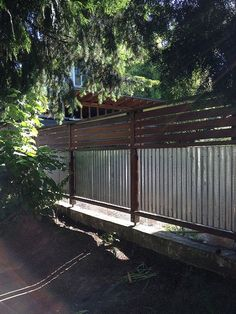 Corrugated metal and wood fence with horizontal slats, semiprivacy, just add bevelled square fence-post tops.