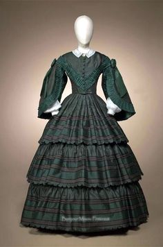 Afternoon dress ca. 1860–62. Green & brown iridescent silk bodice with wide pagoda sleeves, topped with strips of green pleated silk. Wide flounces on the skirt of green, black, & white striped silk. Gemeentemuseum Den Haag via ModeMuze