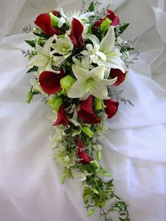 cascading bouquet has a lovely blend of whitecasa blanca lilies and red calla lilies- prettiest bouquet EVER!