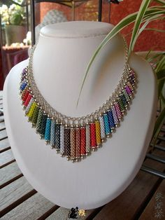 These are beaded but I'm thinking graduated color paper beadsI don't like the materials but I do like the multi colored concept.Seed bead necklace with Daisy Love the technique.This Pin was discovered by Pan Seed Bead Necklace, Seed Bead Jewelry, Bead Jewellery, Beaded Jewelry, Handmade Jewelry, Seed Beads, Beaded Earrings, Jewelry Necklaces, Beaded Necklace Patterns