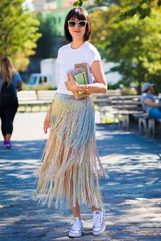 Eva Chen wearing a white t-shirt, a metallic fringe midi skirt, white converse sneakers, beige cat eye sunglasses and a beige clutch. #ootd #outfitideas #minimalstyle #streetstyle Summer outfit, hot day outfit, midi skirt outfit, casual outfit, summer style, hot weather outfit, comfy outfit.