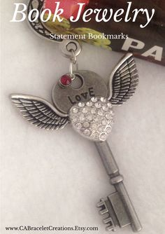 Reading is key with this romantic key bookmark. There is so much to see on this charming piece. Accented with a red gem, this bookmark is perfect for journals and hardcover texts. A beautiful accent piece for those who love to read.