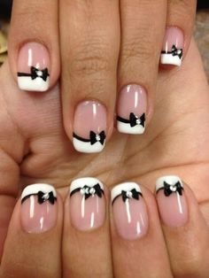 The classic white stripe of short french manicure does not look dull because a spectacular black pattern and fun bows set off it. This design suits romanti