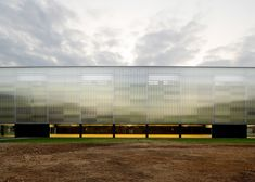 Sports hall covered in translucent panels, giving the building an ethereal quality that helps it match the colours of the sky