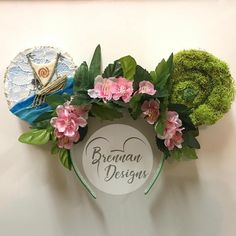 Bring a little magic into your life with these mouse ears inspired by the heartfelt story of Disneys Moana. Wire ears crafted out of white lace, multiple felt colors, moss, bright green sparkle, and artificial pink flowers with leaves. Design styled on a 1-inch headband; one size