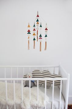 """My leather triangle mobiles are 100% handmade from 100% leather. Each triangle is cut by hand and sewn together with care.This brand new color-way features: - Red- Platinum- Mustard- Hunter Green- Cream Brown fringeMobiles measure approx: 20"""" from tip of wire to the bottom of the fringe, and about 12"""" in diameter.I have done my best to capture accurate colors. But please note, no two pieces of leather are the exact same color, and tones may vary..."""