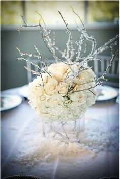 White table flower decoration center, with sparkle spray painted twigs.