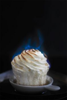 That cupcake is on fire! Flaming Baked Alaska cupcakes! If you're unfamiliar with Baked Alaska it is a dessert composed up of ice cream layered with sponge cake topped with a meringue that's then placed in a super hot oven to set the meringue and brown the top. Because of all this meringue and short trip in a high heat oven the ice cream is actually protected from melting!