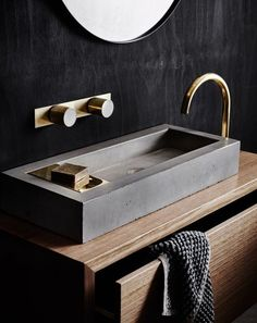 a wooden vanity with a concrete sink and brass details look chic