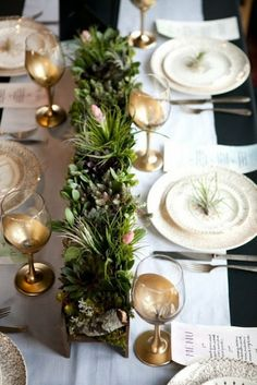 Holiday table setting with gold wine glasses and green plants in a gold rectangular vase separating the two sides of the table