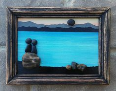 FREE SHIPPING  This will be made to order:  Pebble family of three on vacation (any number of people can be added and/or pets). Set on a hand painted background. Materials used are pebbles, rocks, shells, dried moss, desert plants/twigs.  The frame is open, measuring 8.5x11, also painted in acrylics, and given a distressed look...ready for display on a wall.  Thank you so much for looking. Please message with any questions....P.S. I love special requests....and dont forget to check out my…