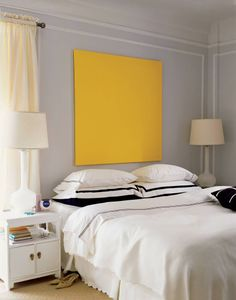 A piece of stretched canary yellow canvas doubles as art and a striking alternative to a headboard | domino.com
