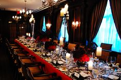 Victorian Halloween Dinner table - candelabras, red roses and black feathers.