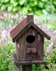 birdhouse placed on a pole with tin roof.