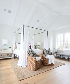 Breezy canopy bed in spacious bedroom with two woven chairs at the foot of the bed