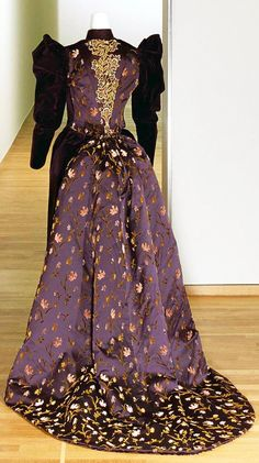 Purple velvet gown, Hirsch Cie N.V., circa 1893, with multicolored floral appliqués. Long-sleeved bodice with pink, yellow, and green embroidery. Side panels of purple silk with flowers woven in. Boned and lined with cream satin. Velvet skirt with embroidered silk train, lined in purple silk. Via Rijksmuseum.