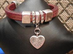 Thick gorgeous distressed brown regaliz leather bangle with 5 piece silver bead set with heart dangle. Detailed embossed end caps with easy