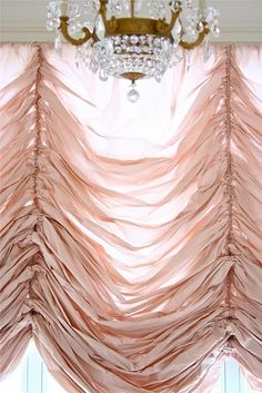 blush pink gathered curtains and crystal chandelier