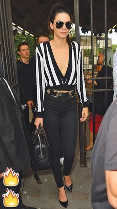 Kendall Jenner in a striped, low-cut sweater, skinny jeans and statement belt