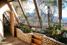 Mountain views from earthship. Indoor garden bed with glass bottle wall. Built in shelf. Greenhouses For Sale, Wooden Greenhouses, Natural Building, Green Building, Earthship Home, Natural Homes, Earth Homes, Sustainable Architecture, Residential Architecture