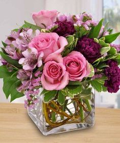 Elegant flowers....small square vase, stems cut short on flowers and as many as possible inserted into vase.