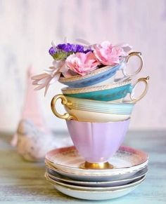 Pretty stacked pastel teacups and saucers used as a flower vase. Just one of the many uses for vintage teacups.