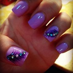 Purple polish background with feather like details on top in black polish and multi colored beads on top.