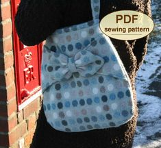 """DESCRIPTION:    Please note: If you wish to make a few bags from Charlie's Aunt sewing patterns or books to sell, please read the rules in the additional information section of our policies page. Inspired by the simple elegance of 1940s fashions but with a modern twist, the """"Village Post"""" Bag PDF SEWING PATTERN is easily constructed with dart shaping, shoulder strap, bow front panel trim and internal zip pocket. The Village Post Bag measures 15"""" (38cm) tall by 14"""" (36cm) wide excluding…"""