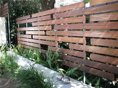 the neighbors. The random horizontal arrangement of the boards along with the visible aluminum posts and fasteners crea