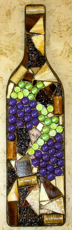 mosaic glass wine bottle wall hanging made using a wooden base, colored glass, colored gems and wine corks.