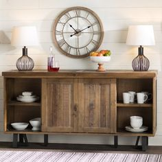 Function gets a dash of farmhouse flair with this stylish sideboard. Crafted of both solid wood and recycled pine, this decorative design is founded on a geometric black-finished base. Each of its two sliding cabinet doors offers a classic slatted design, while distressed details and knots bring out this piece's rustic charm. Use its two open storage shelves on either side to tuck away heirloom metal trays and playful mason jar glasses in the dining room, so you're ready to entertain ...